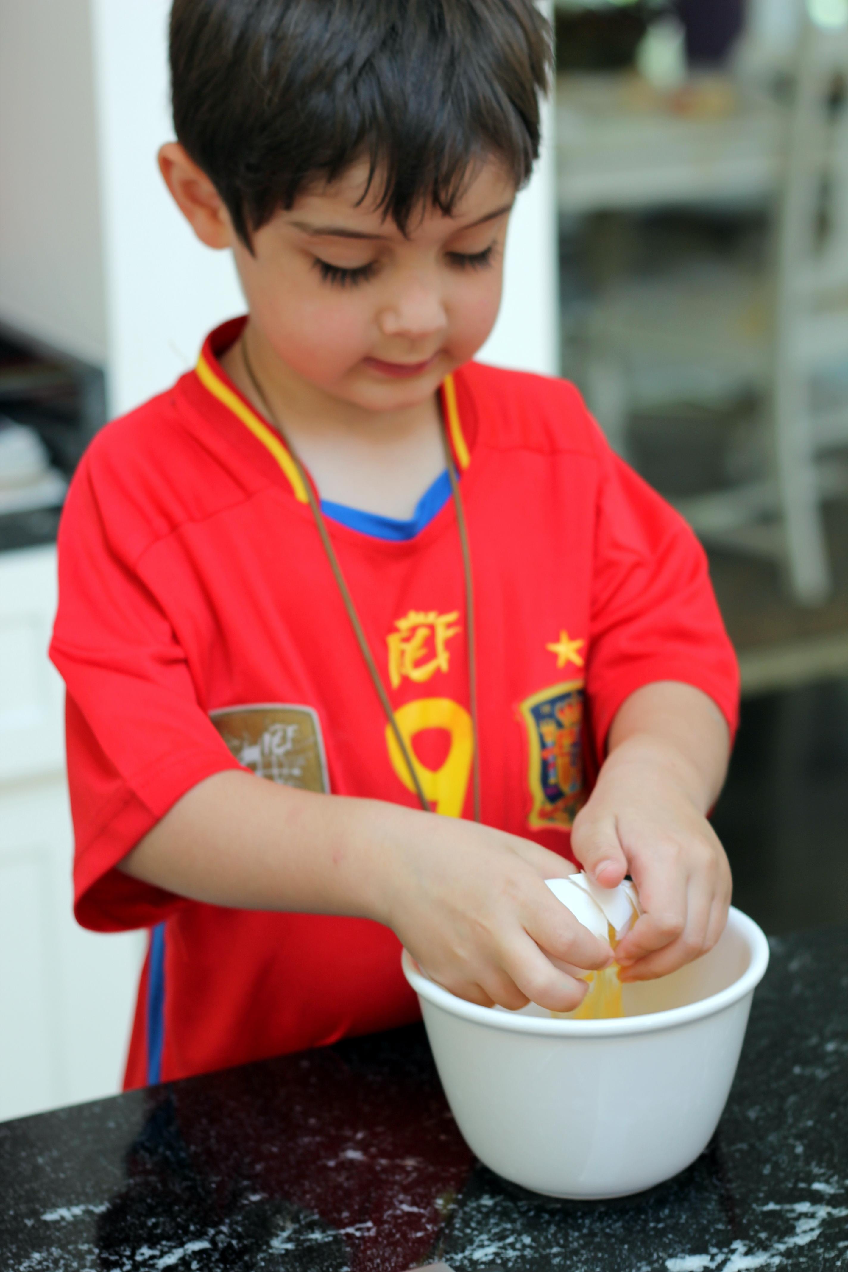 Young boy cracking an egg into a bowl