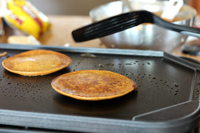 Two pancakes on a griddle