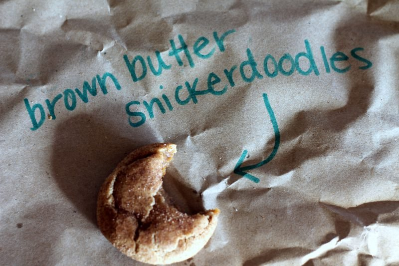 Snickerdoodle cookie on parchment paper with a bite taken out