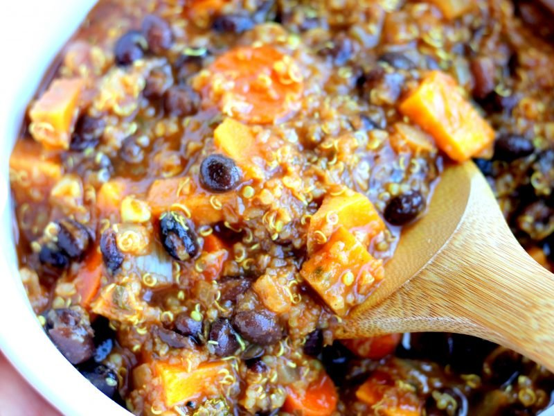 Stirring black bean, sweet potato, and quinoa chili in a pot