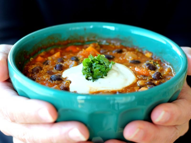 Holding a bowl of black bean, sweet potato, and quinoa chili