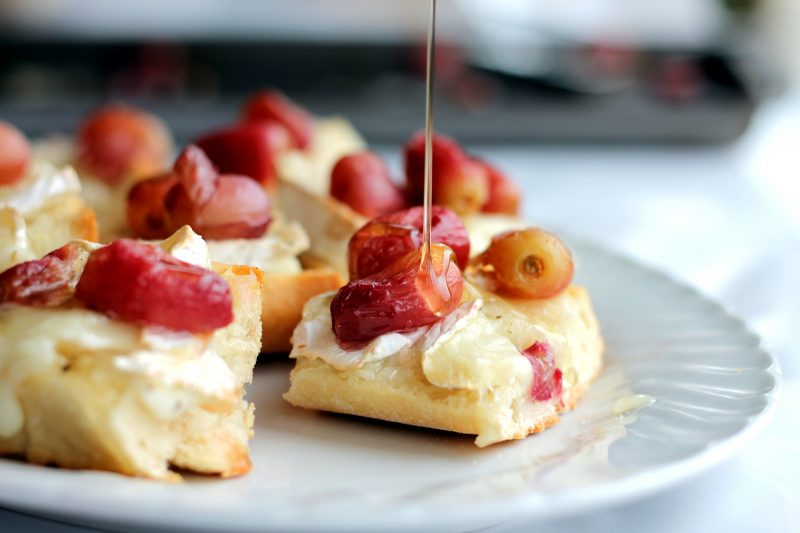 Brie crostini with grapes and honey on a plate