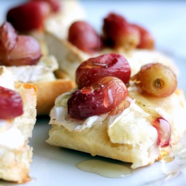 Brie crostini topped with roasted grapes on a plate