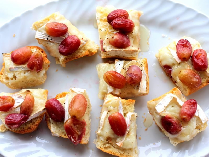 Brie crostini with roasted grapes on a plate