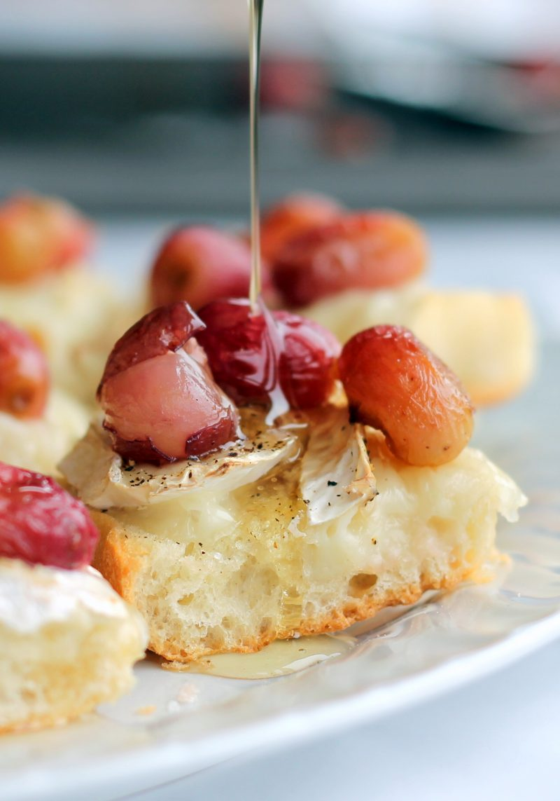 Brie crostini topped with roasted grapes and drizzled in honey