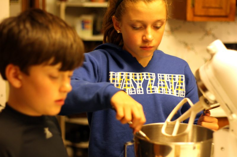 Two kids mixing cookie dough