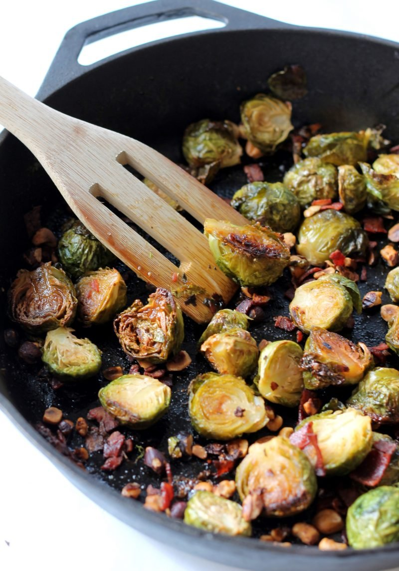 Stirring maple roasted brussels sprouts in a skillet