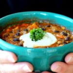 black bean, sweet potato quinoa chili in a bowl topped with sour cream