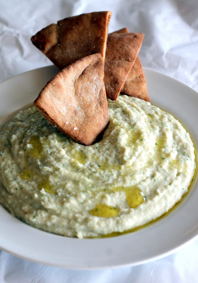 Bowl of white bean basil hummus with homemade toasted pita chips