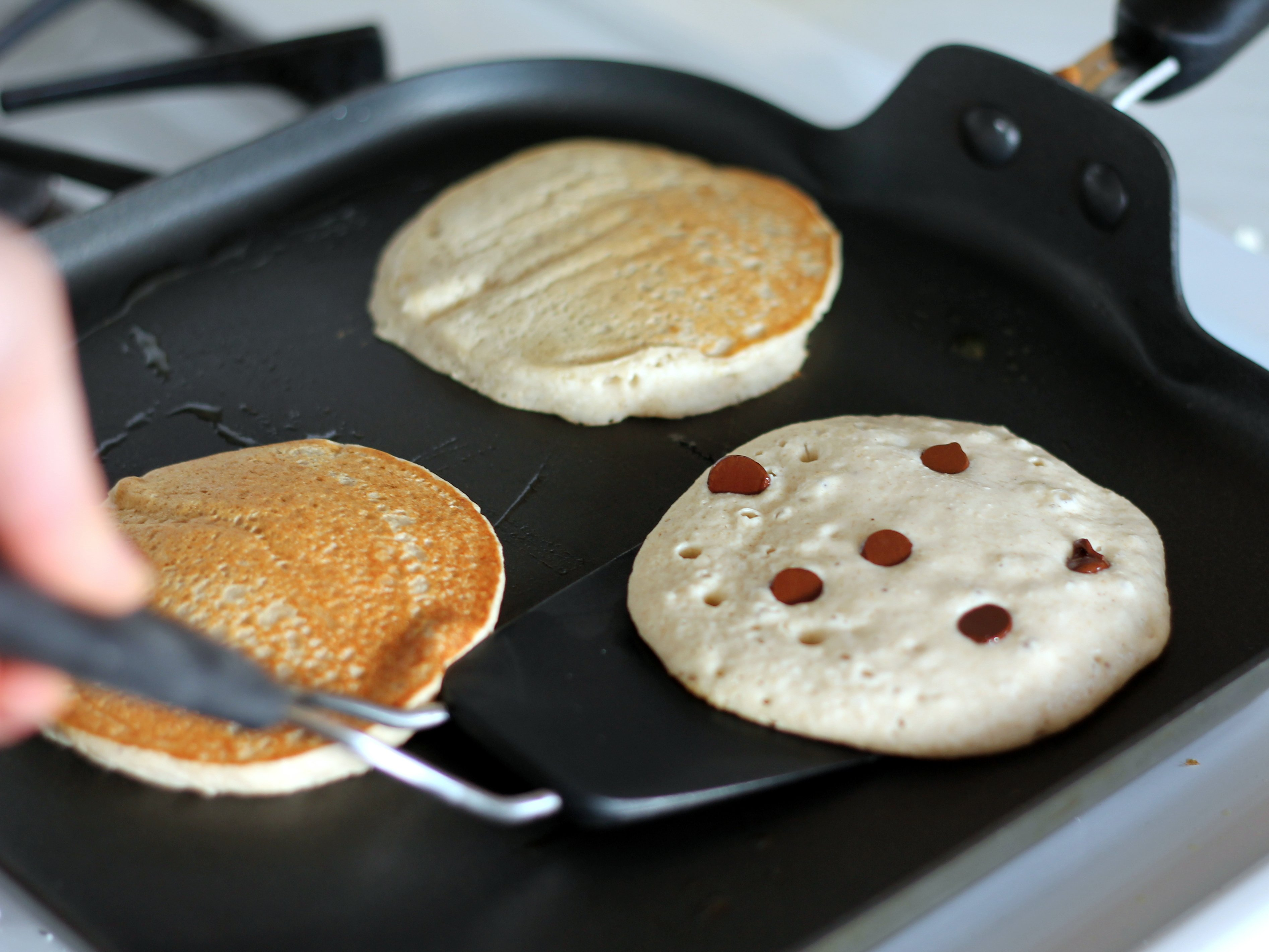 pancakes on a flat griddle almost ready to be flipped over by a spatula