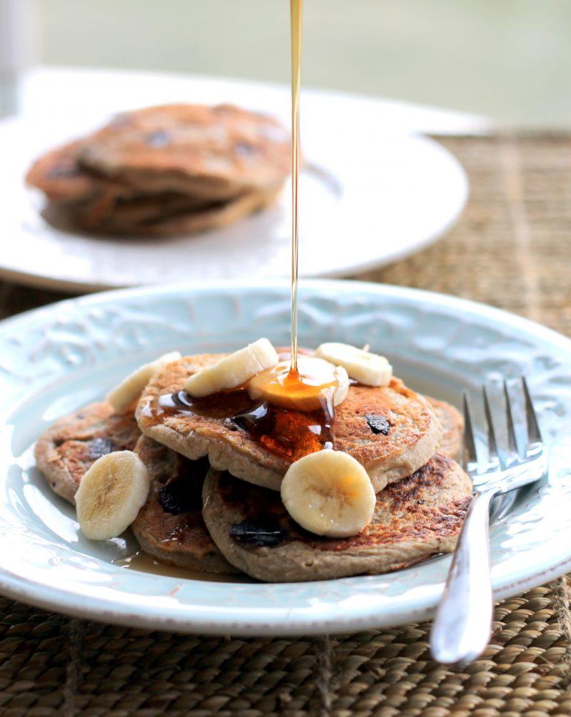 Syrup pouring onto oatmeal chocolate chip banana pancakes