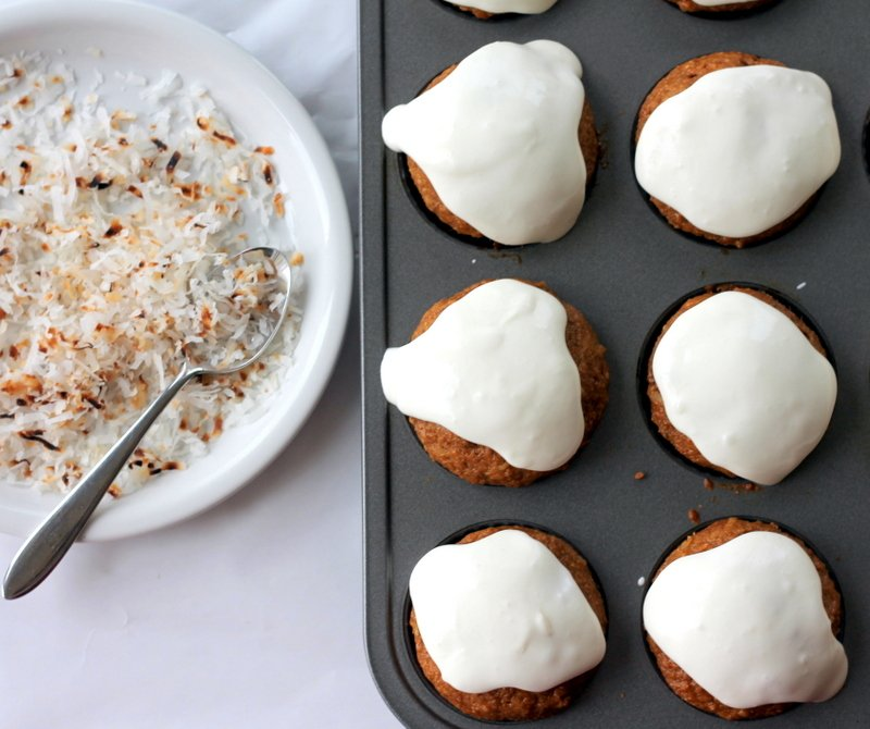 healthy morning glory muffins in a muffin tin next to a plate of coconut