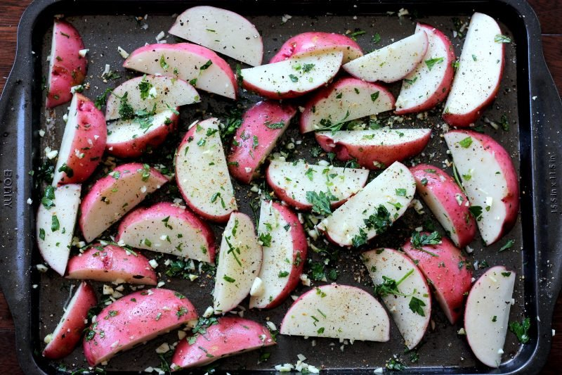 roasted red potato wedges with herbs on a baking sheet