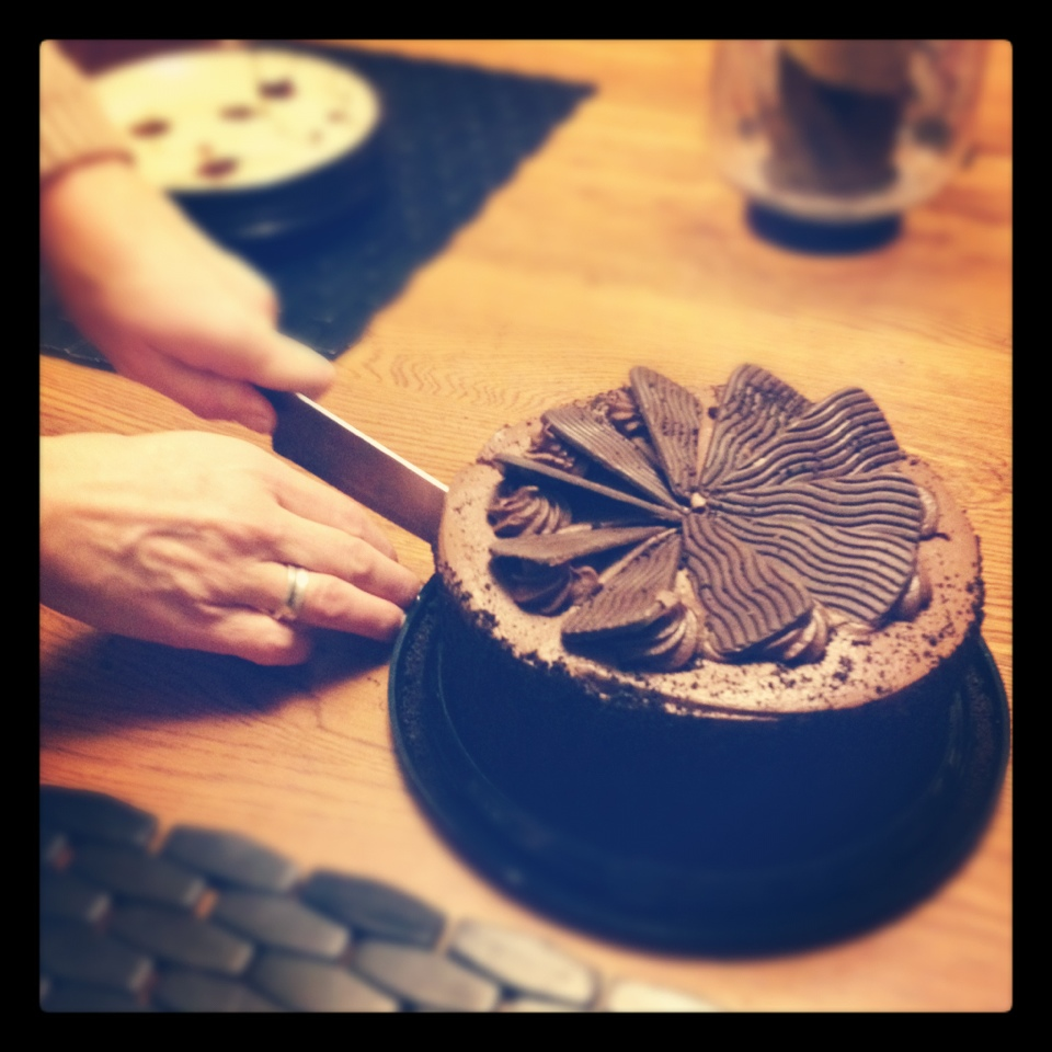 cutting into chocolate cake