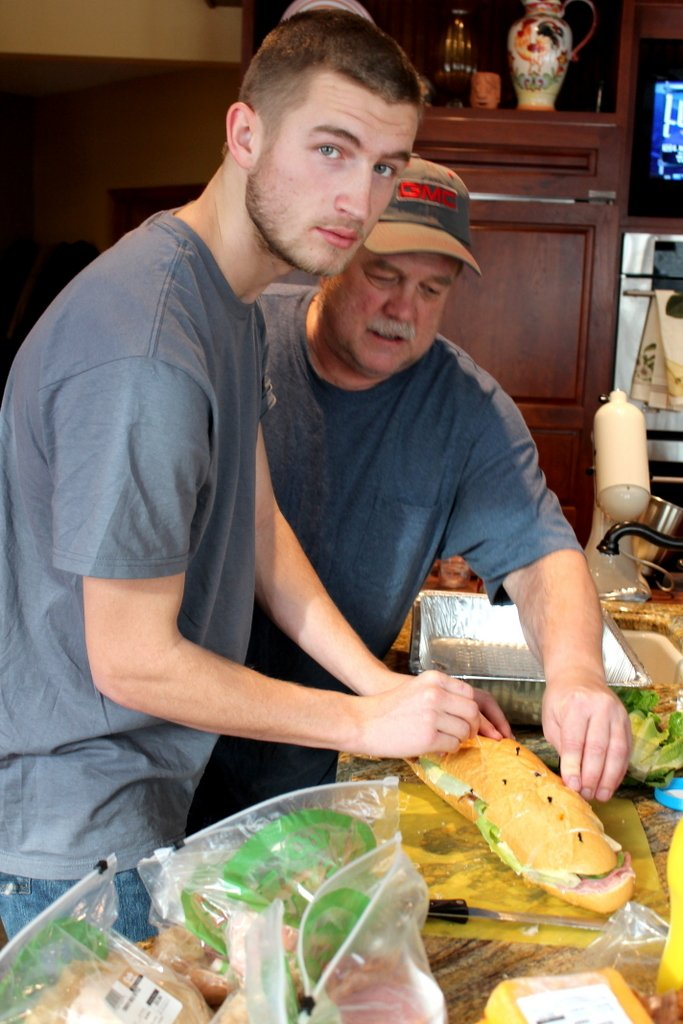 two men making sandwich for football party