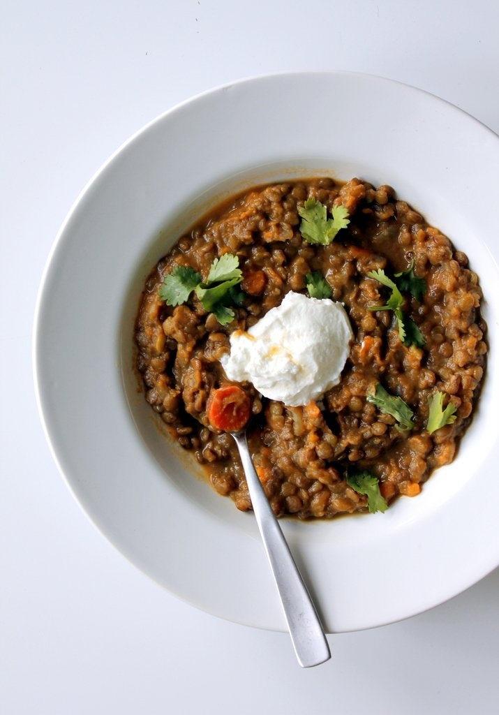 Lentil chili with sour cream and cilantro in a white bowl
