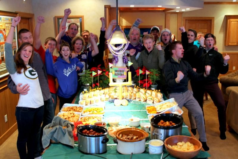 people cheering at football party with table of food