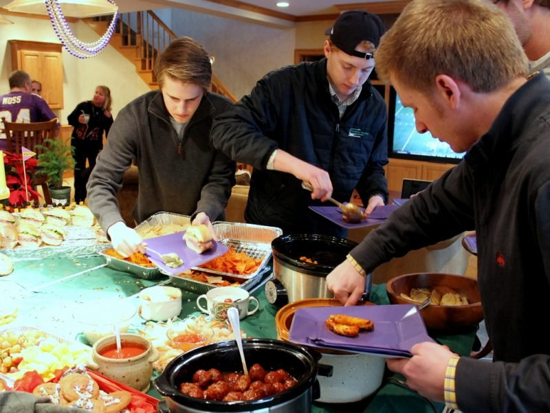 three young men filling plates with football party food