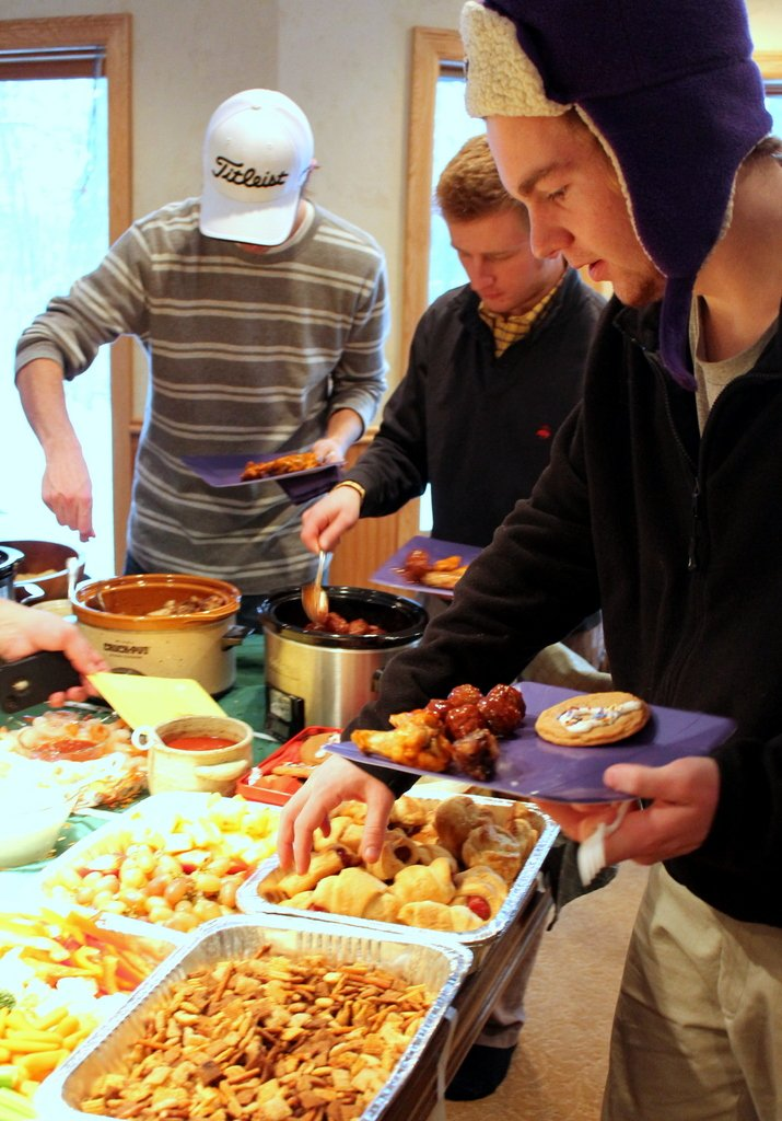 young men filling plates with football party food