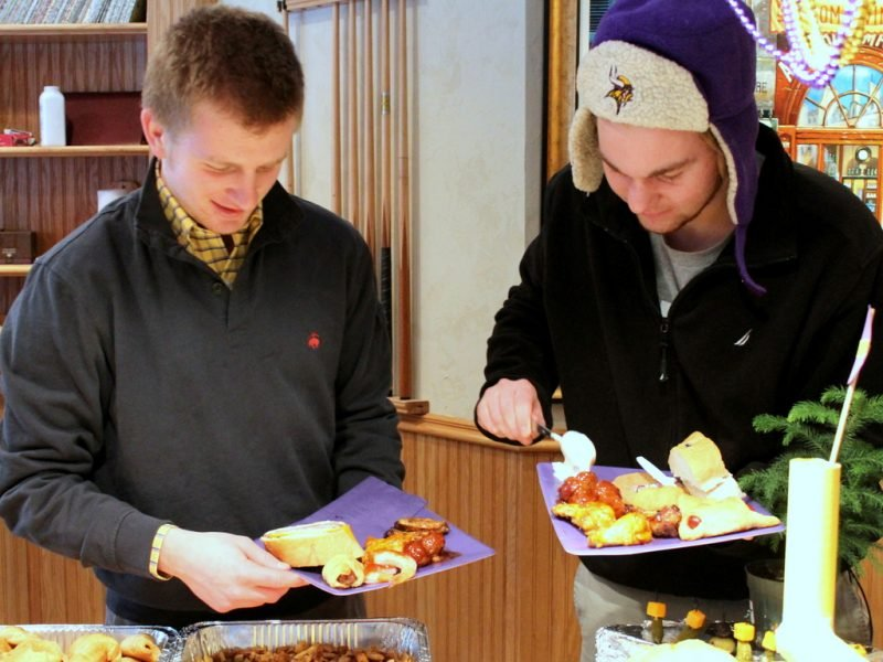 two young men filling plates with football party food
