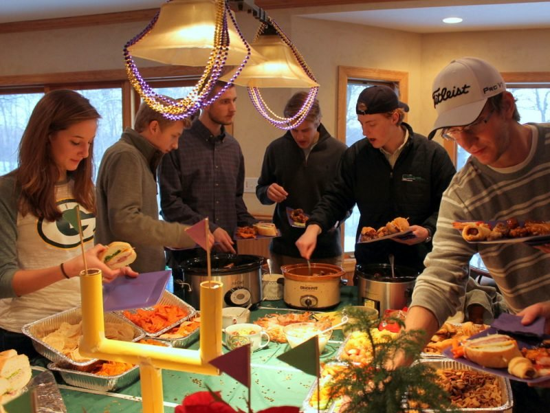 party guests filling plates with football party food