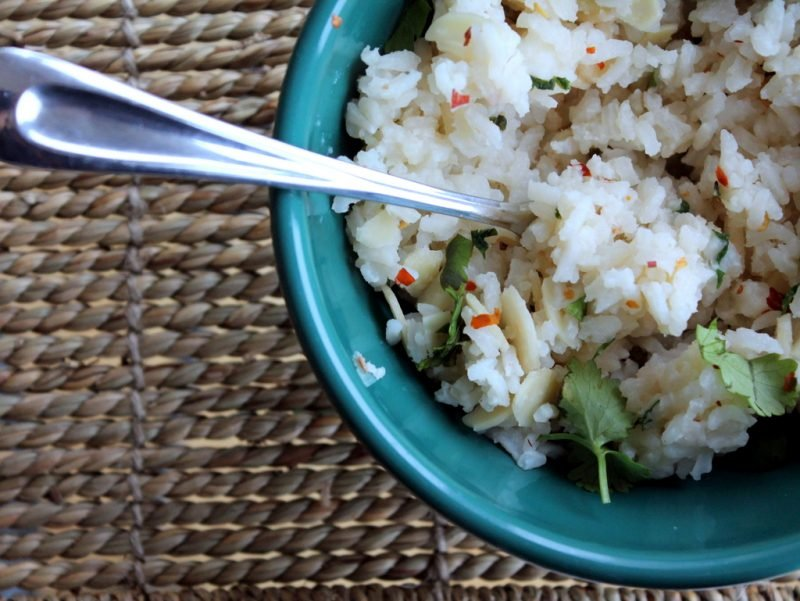 bowl of of rice with almonds and cilantro