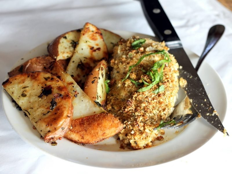 crusted chicken breasts with potatoes on plate