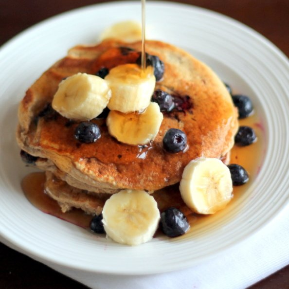 stack of oatmeal pancakes with bananas and maple syrup