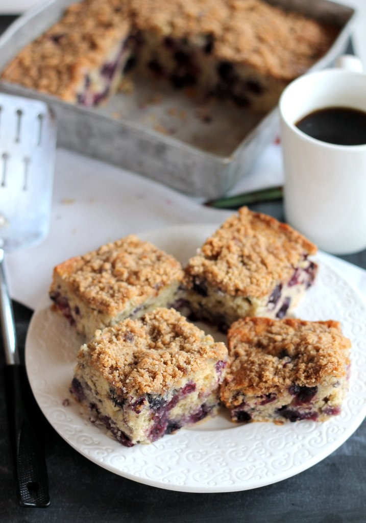 pieces of blueberry coffee cake on plate with cup of coffee