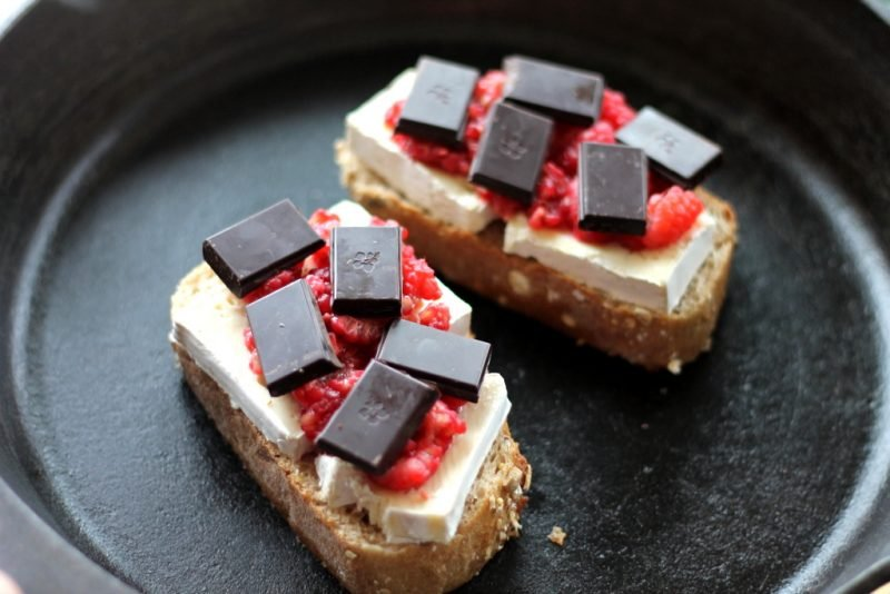 bread with brie, raspberries, and dark chocolate in skillet