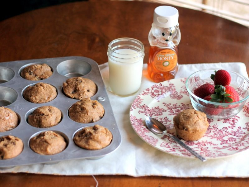 breakfast spread of oat bran muffins in pan and plate with milk and honey