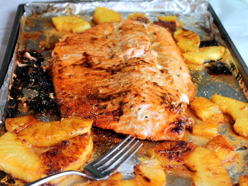 salmon and pineapple slices on baking sheet