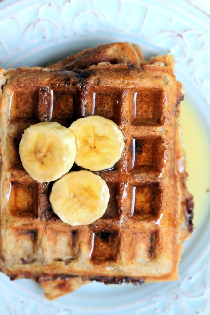 stack of waffles on plate with banana slices and maple syrup