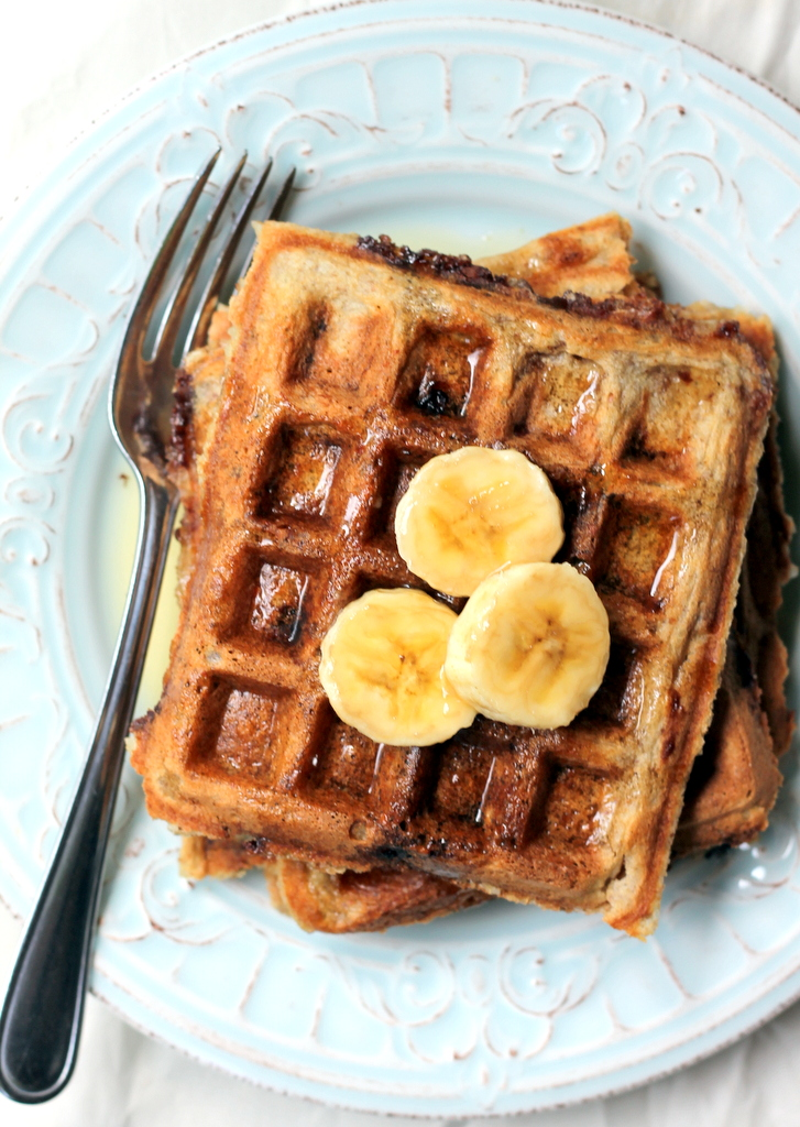 waffles on plate with banana slices and maple syrup