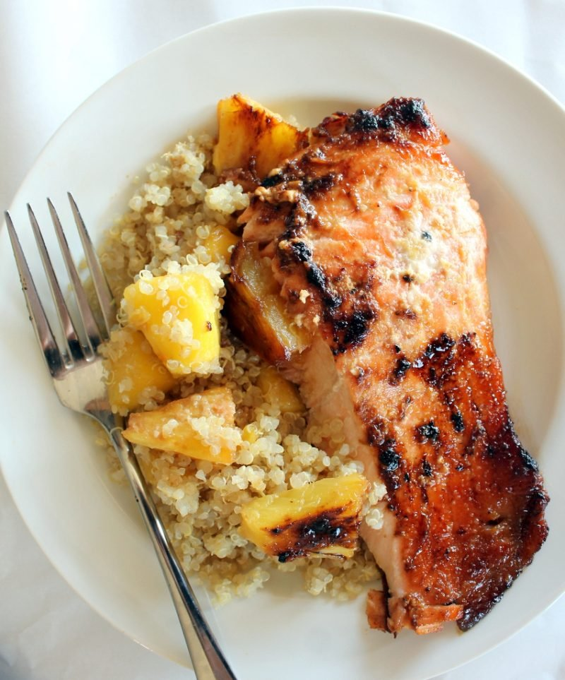healthy salmon recipes: salmon and pineapple over quinoa in a bowl with a fork