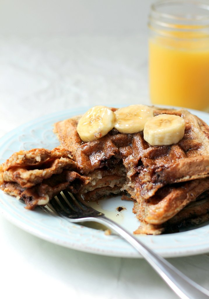waffles on plate with banana slices and orange juice