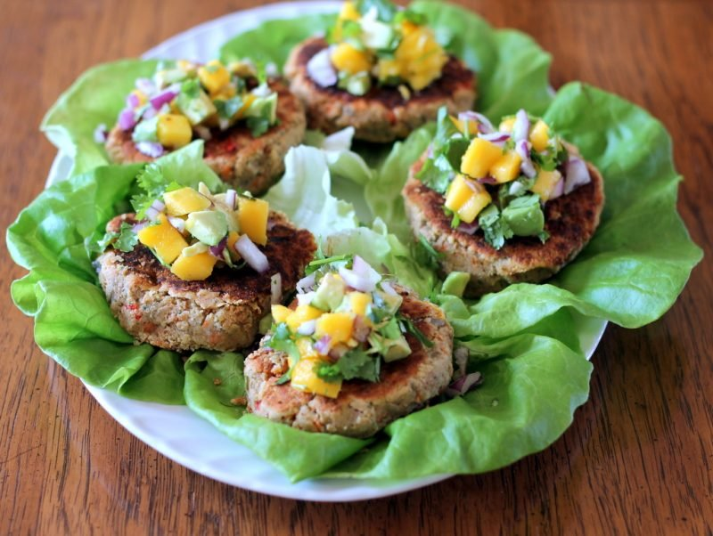 chickpea lentil burgers with mango and avocado on plate with lettuce