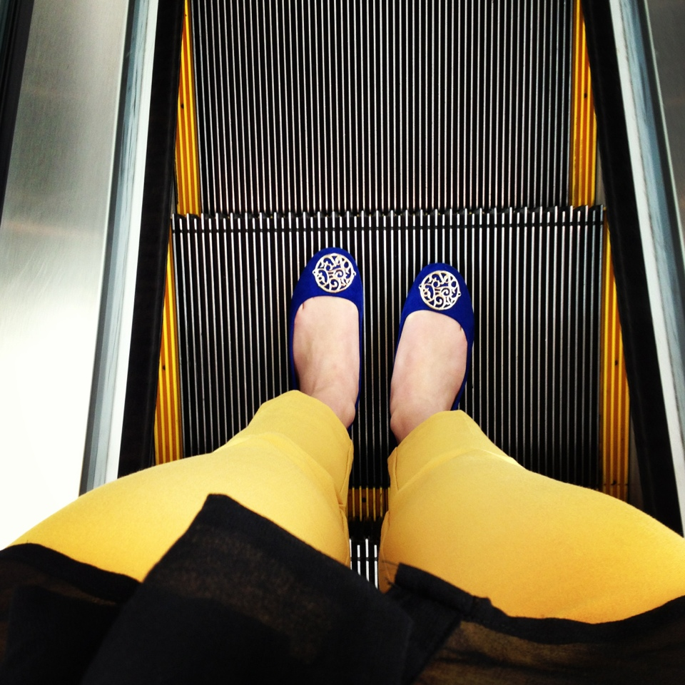 yellow pants and blue flats on an escalator