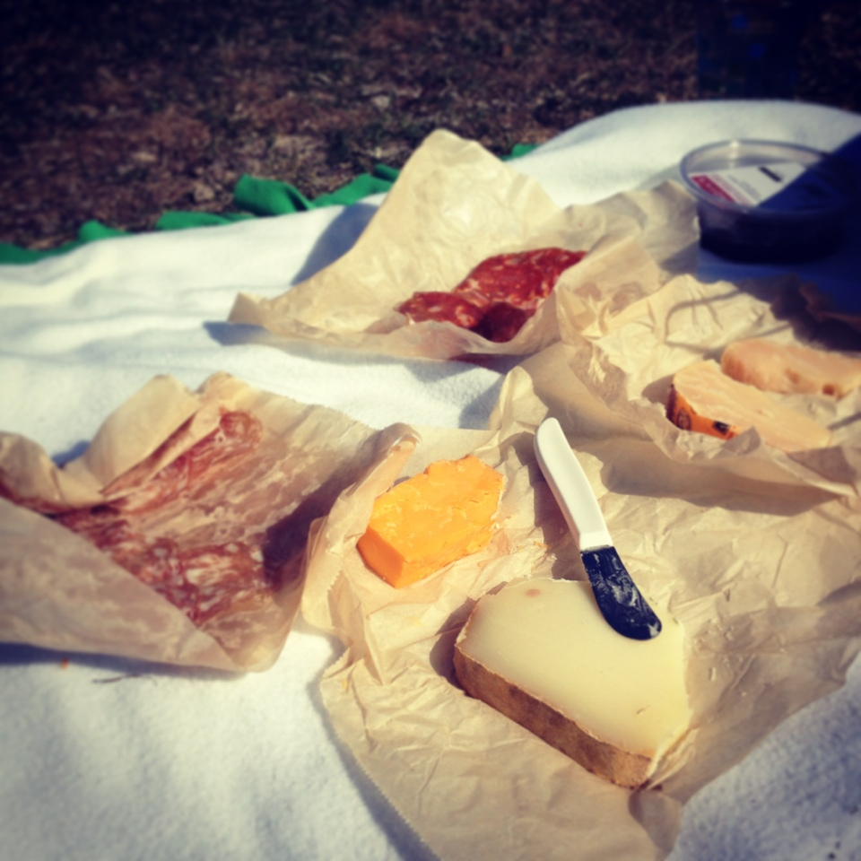 meats and cheese on a a picnic blanket