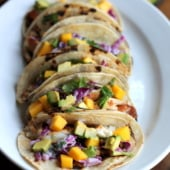 fish tacos on plate with mango and avocado