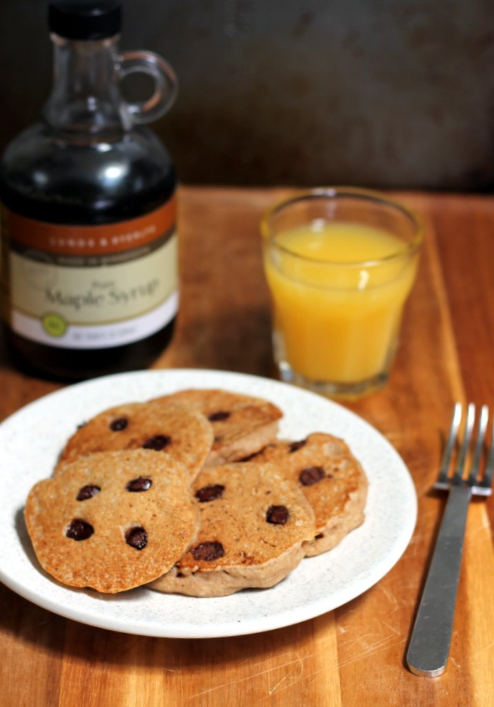 plate of chocolate chip pancakes with maple syrup and orange juice