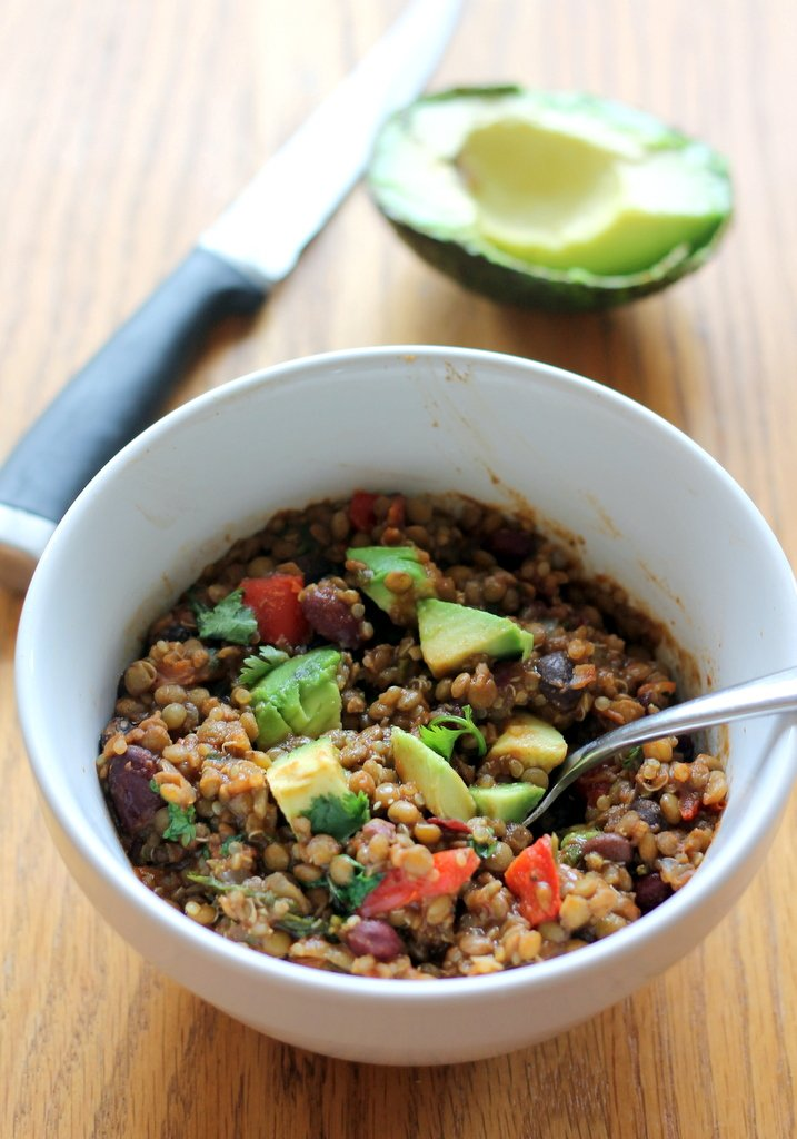 vegetarian lentil and quinoa chili in bowl with avocado