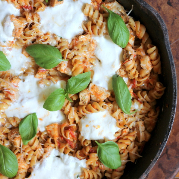 pasta with chicken, cheese, and basil in skillet