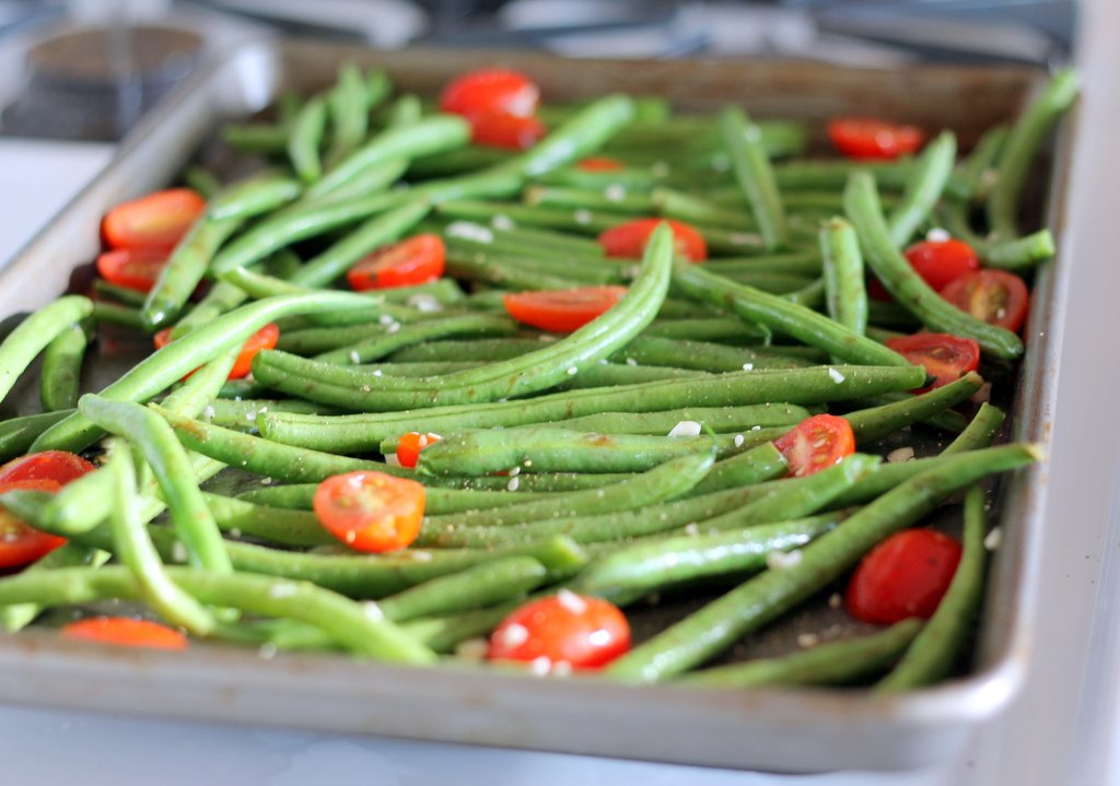 Parmesan green beans and tomatoes on a baking tray