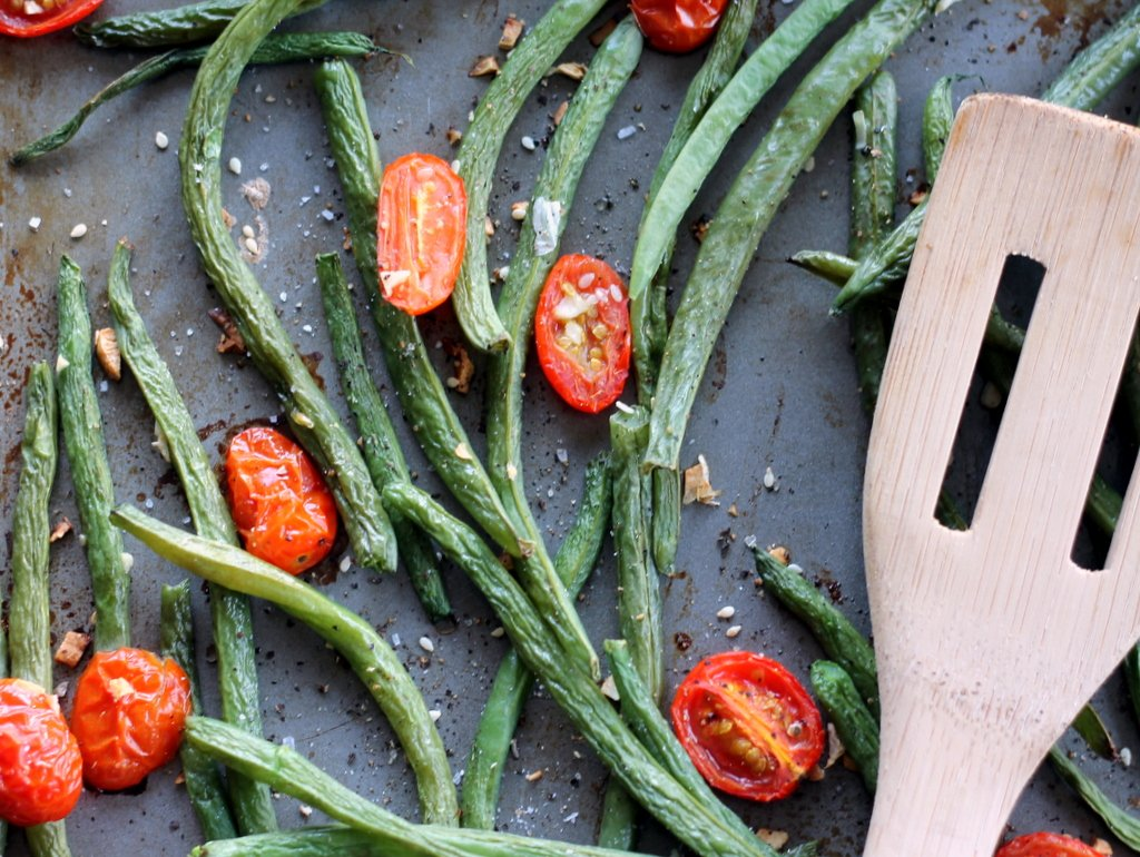 Roasted garlic parmesan green beans with tomatoes on a baking tray