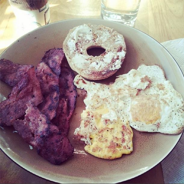 Bacon, eggs, and half of a bagel on a plate