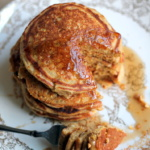cornmeal pancakes stacked and drizzled with syrup