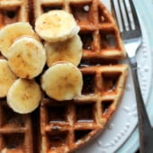 Banana chocolate chip quinoa flour waffles with sliced bananas on top