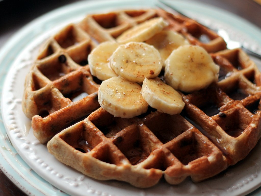 Banana chocolate chip quinoa flour waffles with banana slices on top