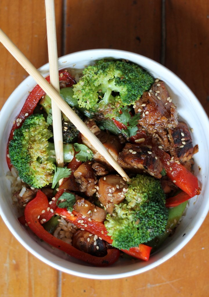 Sesame chicken stir fry in a bowl with veggies and chopsticks